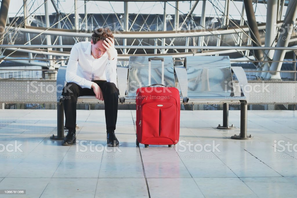 flight delay or problem in the airport, tired desperate passenger waiting in the terminal stock photo