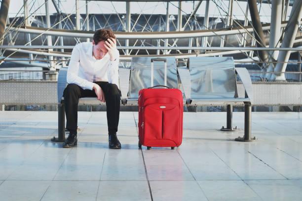 Flugverspätung oder Problem auf dem Flughafen, müde verzweifelter Passagier wartet im terminal – Foto