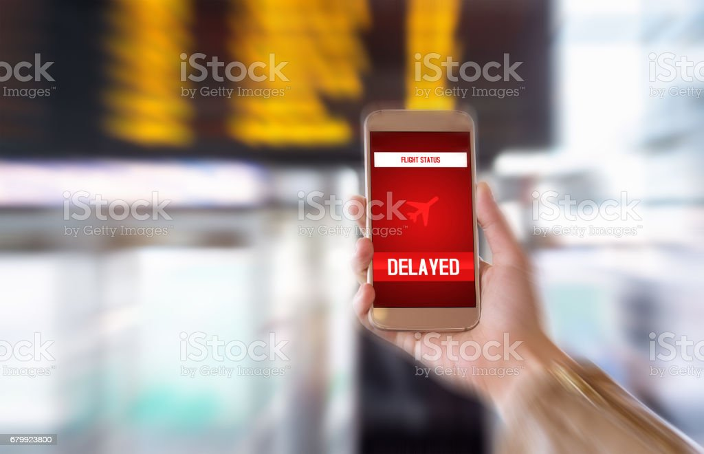 Flight delayed. Delay in flying schedule. Aeroplane will take off late. Smartphone application announces bad news to tourist. Woman holding mobile phone in airport terminal. Timetable background. stock photo