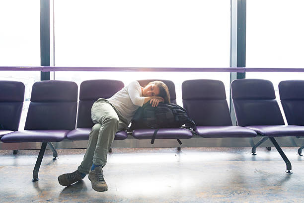 flight delayed Young woman in a airport lounge with jet lag issues.  She's sleeping while waiting her delayed flight jet lag stock pictures, royalty-free photos & images