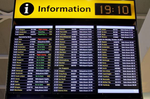 flight information board at airport - arrival departure board stock photos and pictures