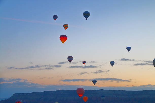 Flight of balloons over a mountain valley at sunrise.