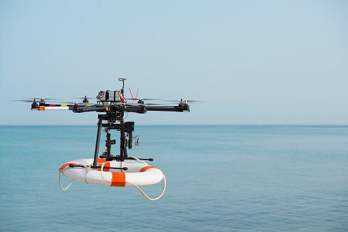 Radio control octocopter (Drone/ UAV) in the air carrying life ring to rescue active drowning victim.