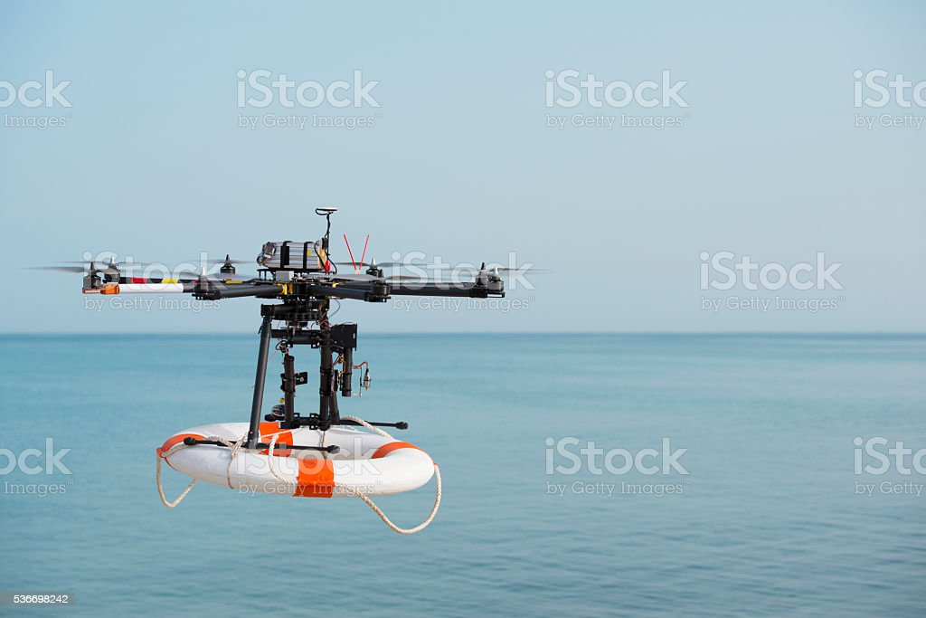 Flight of rescue drone carrying lifebuoy. stock photo