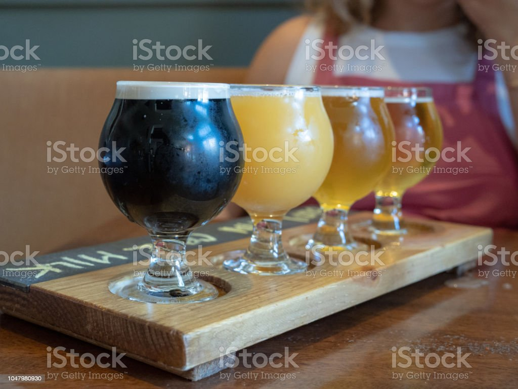 Flight of stout, Amber, IPA beers sitting on wooden paddle stock photo