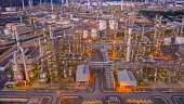 Flight over an oil refinery with pipes and chimneys. Petrochemical plant in twilight under moody dusk sky,drone aerial view