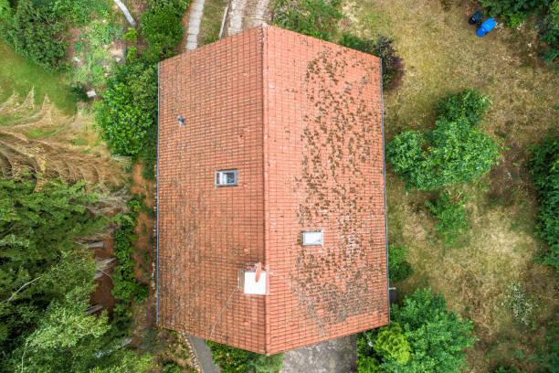 flug über das rote dach einer einzigen familie haus mit einem kamin und einer satellitenantenne für inspektion, kontrolle und vorbereitung für eine reparatur. - aerial view soil germany stock-fotos und bilder