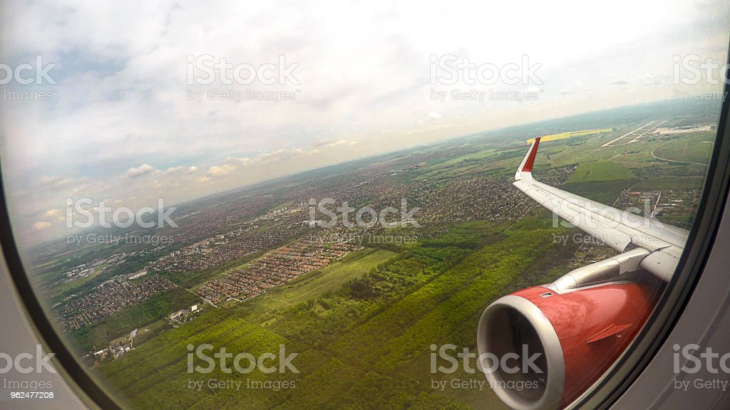POV of flight passenger looking through window at ground, sky and aircraft wing stock photo