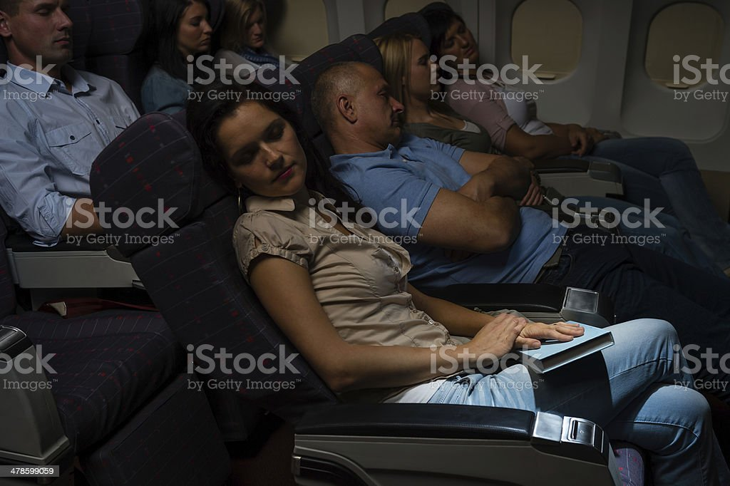 Flight passengers sleep plane cabin night travel stock photo