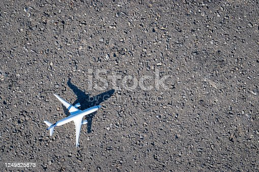 istock Flight plane white toy on dark asphalt background. Bright airplane, fly aircraft in air travel concept. 1249825873