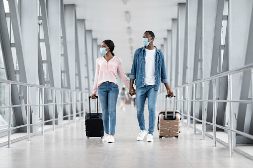 Flight Resumption. Black Couple Wearing Protective Masks Walking With Suitcases At Airport