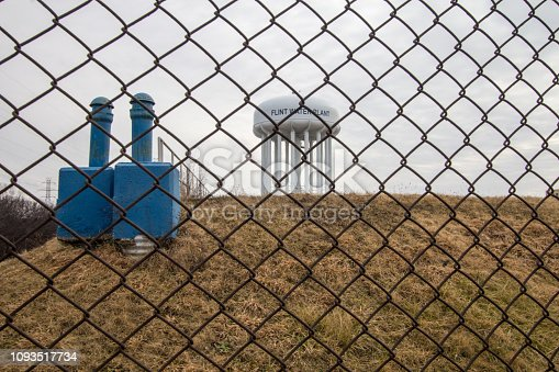 Water tower of Flint Michigan through a chain linked fence. The city came into the national spotlight during the Flint Water Crisis.