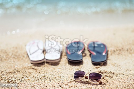 istock Flip Flop and Sunglasses on Summer Beach by the Sea 521207958