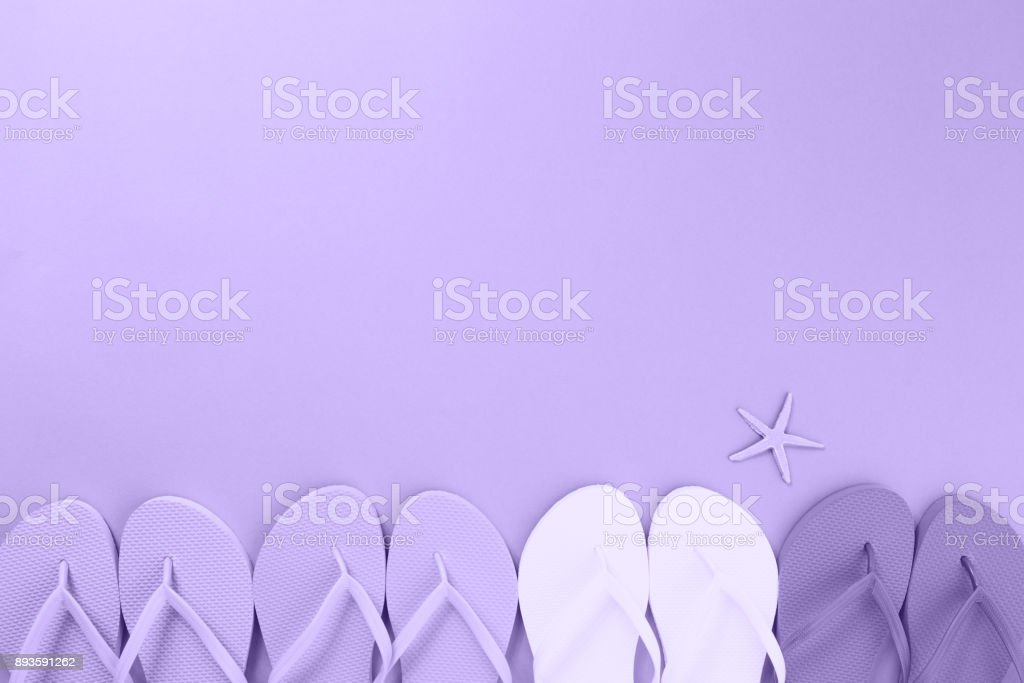 Flip flops and a sea star. Ultra violet tone, color of the year 2018 stock photo