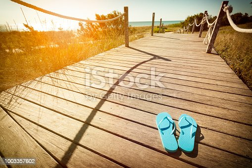Horizontal view of blue flip flops left on a wooden footpath to the beach on the dunes at sunset. Copy space available for text and/or logo. DSRL outdoors photo taken with Canon EOS 5D Mk II and Canon EF 17-40mm f/4L IS USM Wide Angle Zoom Lens