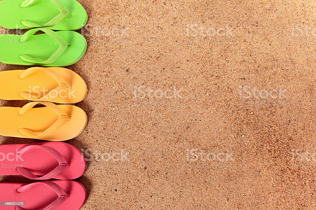 Row of colorful flip flops on a sandy beach. Alternative horizontal...