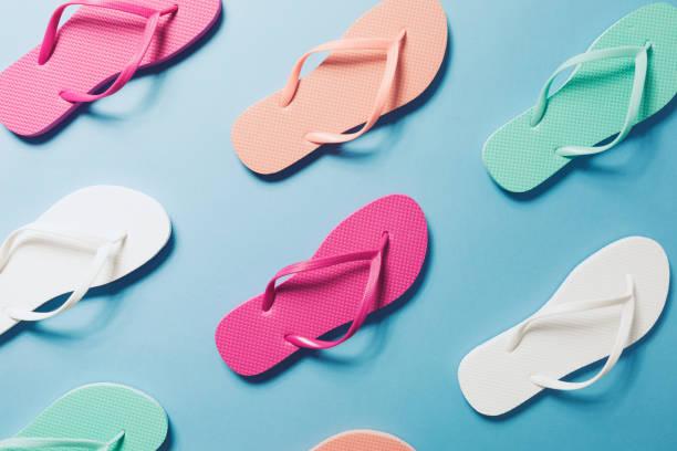 flip flops auf blauem hintergrund - salzwasser sandalen stock-fotos und bilder