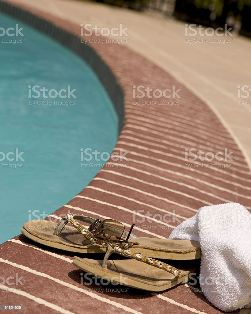 Flip-Flops and  towel by a pool stock photo