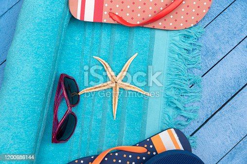 699960484 istock photo Flip-flops, beach towels and sunglasses on wooden table. 1200686144
