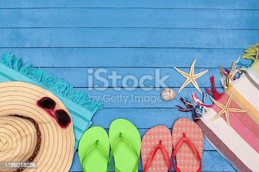 699960484 istock photo Flip-flops, hat, beach towels and sunglasses on wooden table. 1199218236