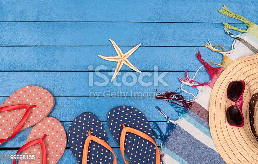 699960484 istock photo Flip-flops, hat, beach towels and sunglasses on wooden table. 1199668135