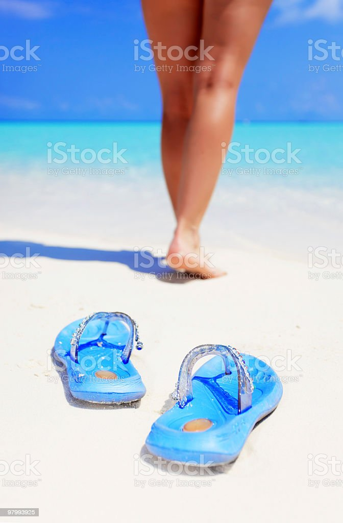 Flip-flops on beach and woman's leg in bacground. royalty free stockfoto