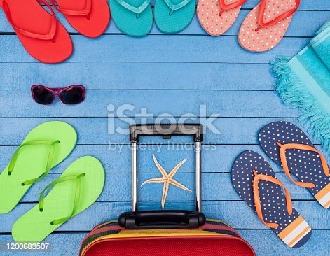 699960484 istock photo Flip-flops, suitcase, beach towels and sunglasses on wooden table. 1200683507