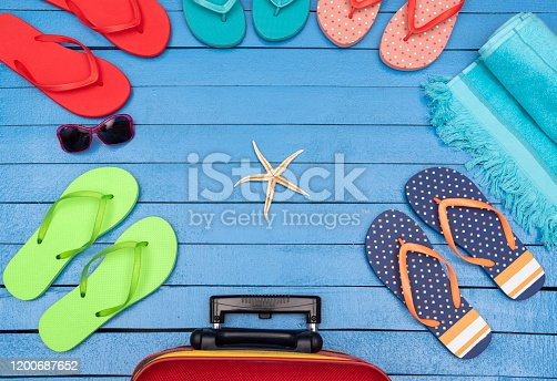 699960484 istock photo Flip-flops, suitcase, beach towels and sunglasses on wooden table. 1200687652