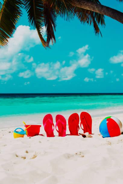 flip-flops, spielzeug und shell am strand - flitterwochen flip flops stock-fotos und bilder