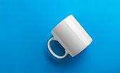 Flipped white mug on blue background - mug template
