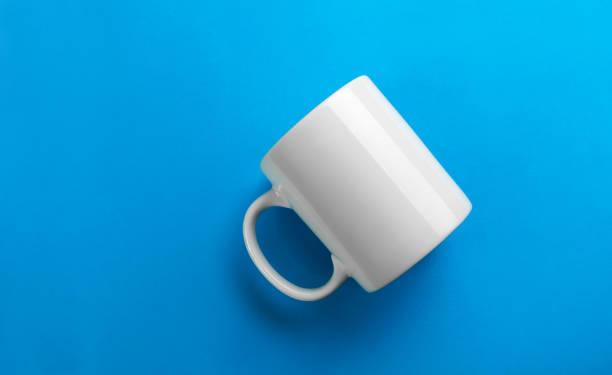 Flipped white mug on blue background stock photo