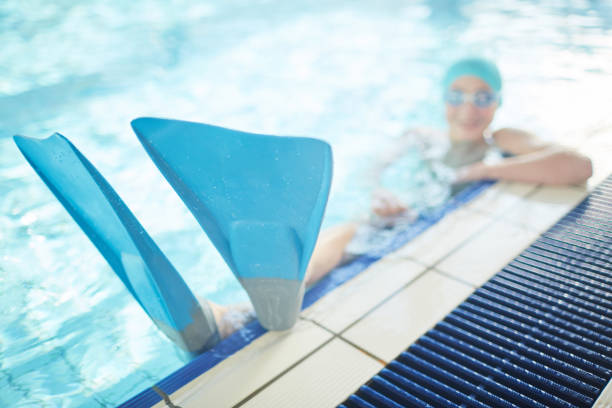 Flippers on swimmer feet Blue flippers on feet of young swimmer enjoying leisure in swimming-pool diving flipper stock pictures, royalty-free photos & images