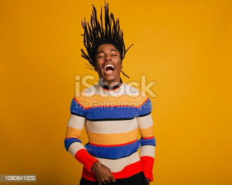 Waist-up portrait of a young man flipping his hair in front of a yellow background. He is wearing a striped sweater.