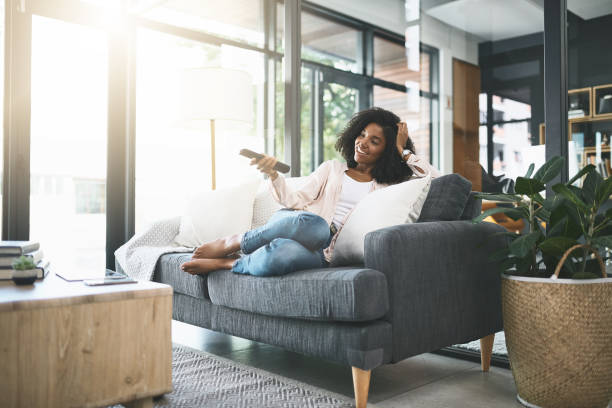 Flipping through the channels Shot of an attractive young woman relaxing at home watching tv stock pictures, royalty-free photos & images