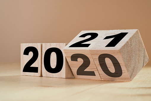 istock Flipping wooden cubes for new year change 2020 to 2021. New year change and starting concept. 1205544619