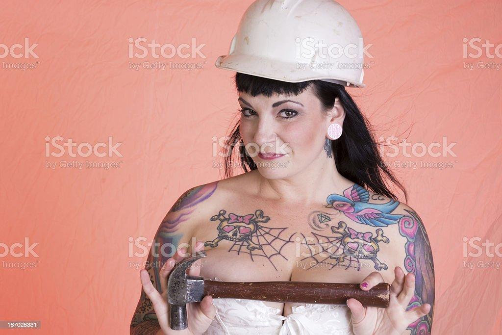 Flirtatious pinup model holding hammer across chest. royalty-free stock photo