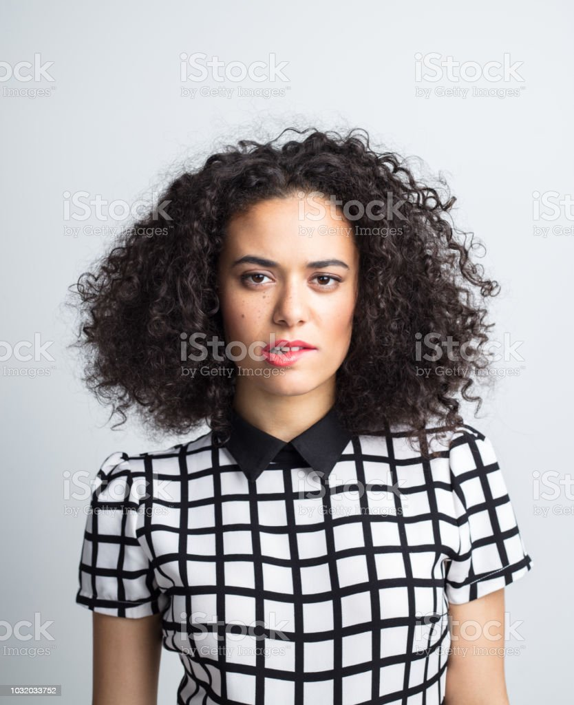 Flirtatious woman biting her lip Portrait of young beautiful woman biting her lip on gray background. Female with curly hair wearing casual outfit flirting on gray background. 20-24 Years Stock Photo