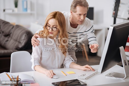 istock Flirting boss hugging young secretary in the office 664668094