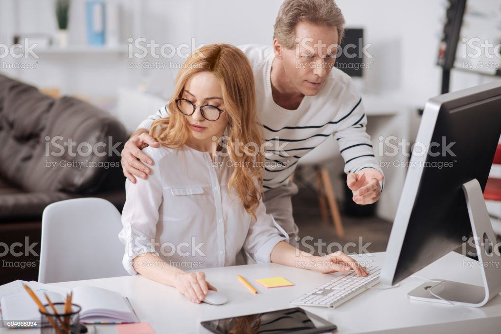 Flirting boss hugging young secretary in the office stock photo