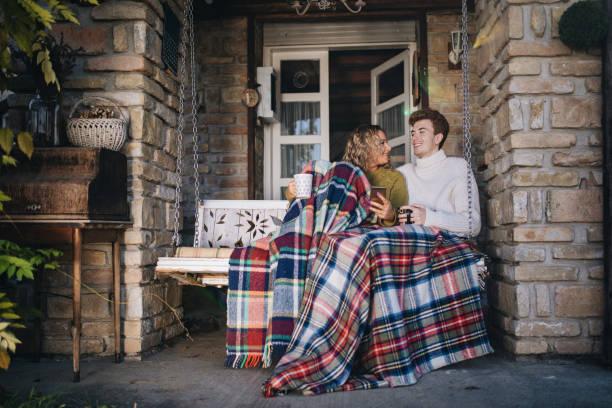 flirten paar genießt heißen kakao im freien auf der veranda - veranda decke stock-fotos und bilder