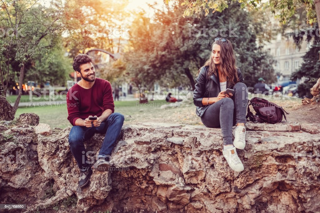 Flirting couple in the city park stock photo