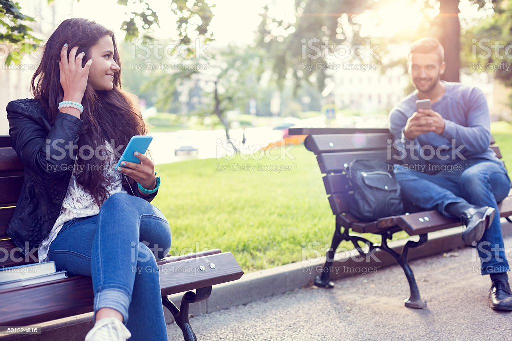 Flirting couple in the park stock photo