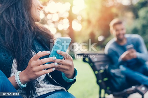 Happy couple using smartphones in the city park