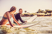 Loving couple of surfers in the water, flirting while waiting for a good wave to come