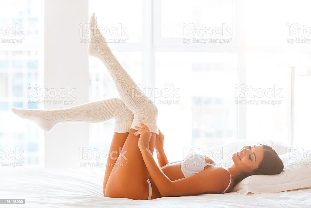Flirty beauty in bed. stock photo