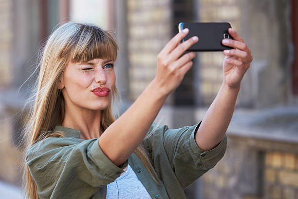 Flirty girl posing for selfie Beautiful woman flirting for self portrait puckering stock pictures, royalty-free photos & images