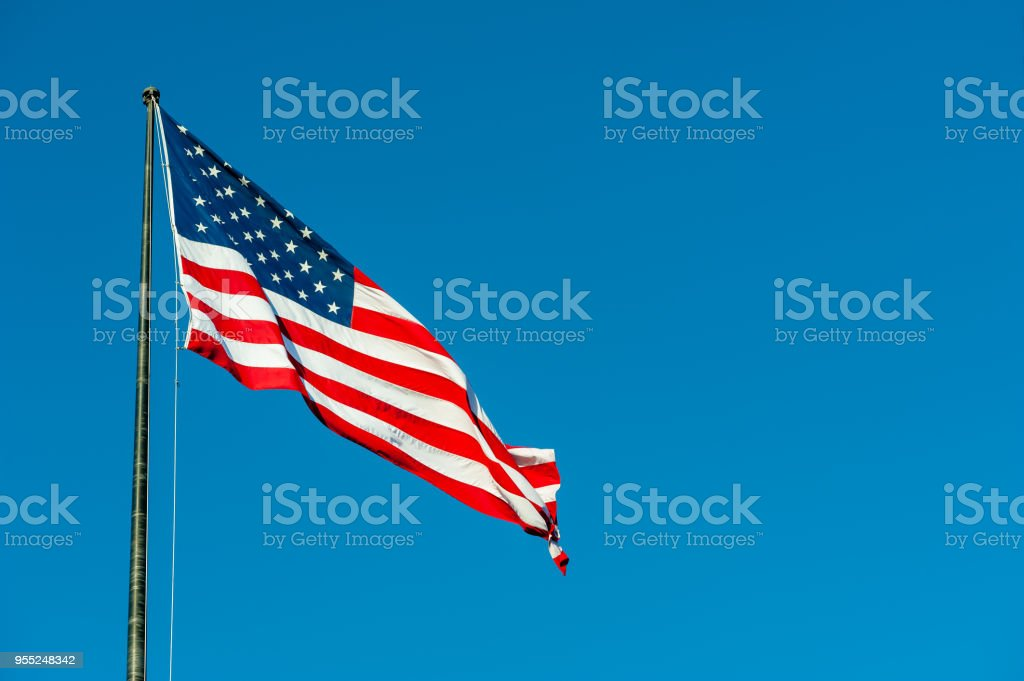 Floating american flag against blue sky stock photo