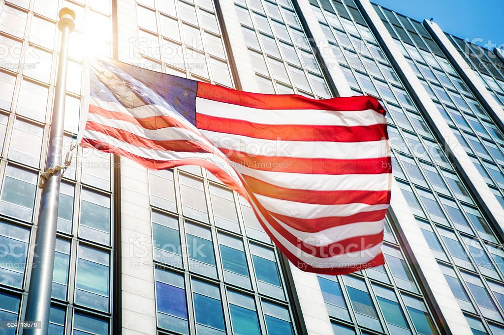 Floating American flag in front of office building sun flare stock photo