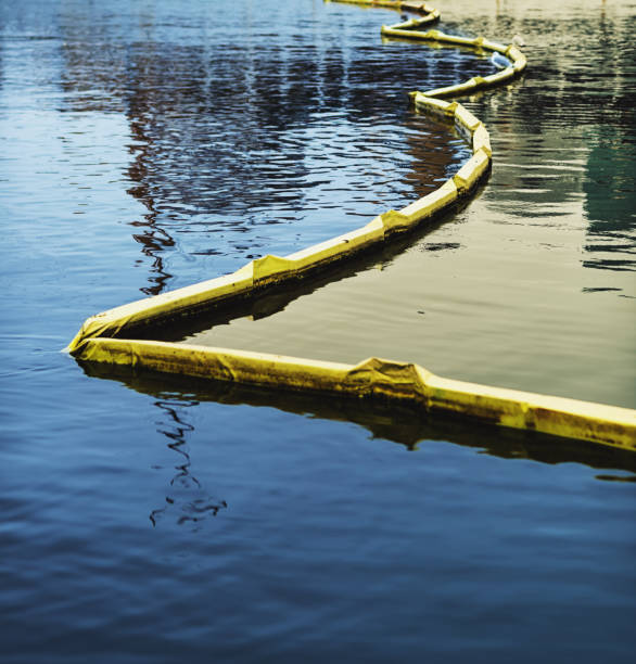 Floating Anti-Pollution Barrier Floating boom barrier containing a film of oil and dirt. environmental cleanup stock pictures, royalty-free photos & images