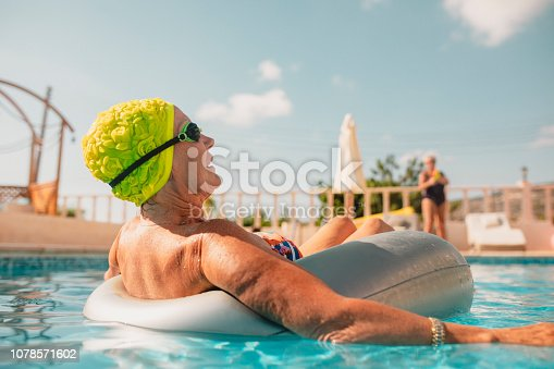 Senior female adult relaxing in an inflatable ring in the swimming pool. She is on holiday in Paphos, Cyprus.